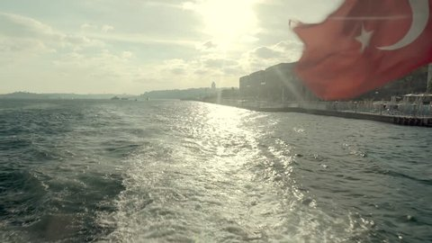 Turkish Flag On Side Of Boat.Flag On Boat Ship In The Wind in Istanbul at Sunset.Vivid Red Turkish Flag Flutter On Wind Against, Stern Of Ferry Boat.Red flag on a boat.Red Turkish Symbol Flap On Wind.