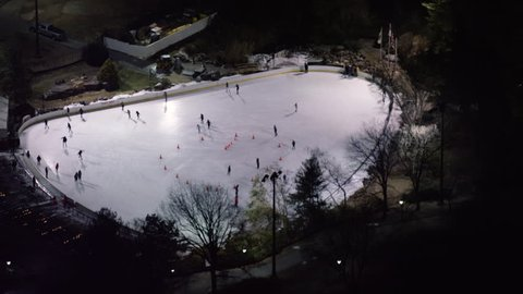 Aerial view of people skating on an outdoor skating rink in winter at night in New York City, with dark nighttime lighting. Shot on 4k RED camera on helicopter.