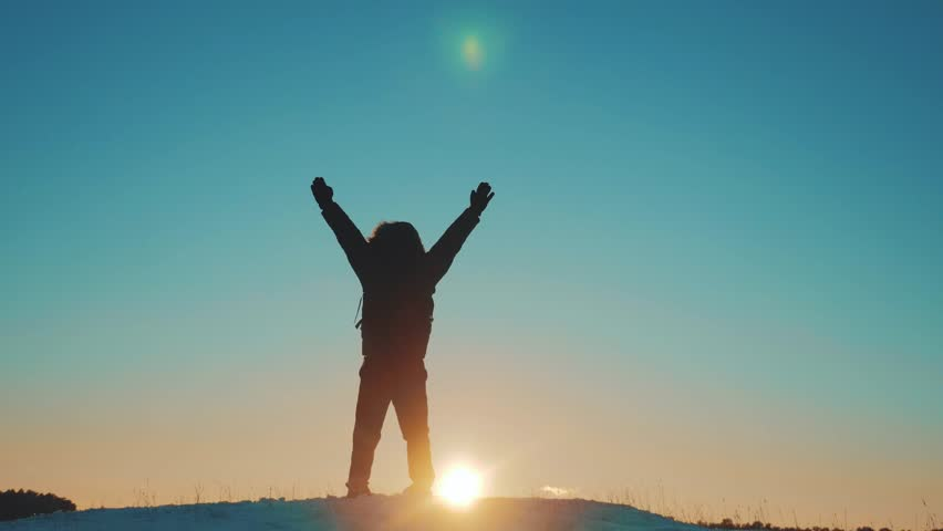 man tourist raised his hands up success victory stands on top of a mountain silhouette winter. Dawn sunrise sunlight tourist travel. Happy Hiker silhouette of man standing on lifestyle the mountain