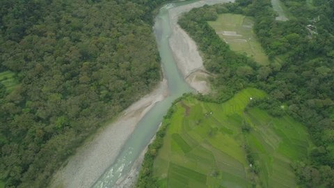 Aerial view mountain valley, river, rice fields, farmland in Philippines, Luzon. Aerial view mountains covered forest, tree. Cordillera region.