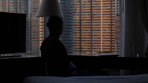 Man stand up and go away from table, silhouetted shot against room window. Dim natural light, large mansion building seen blurred outdoors. Guy has finished work, laptop lie closed on desk