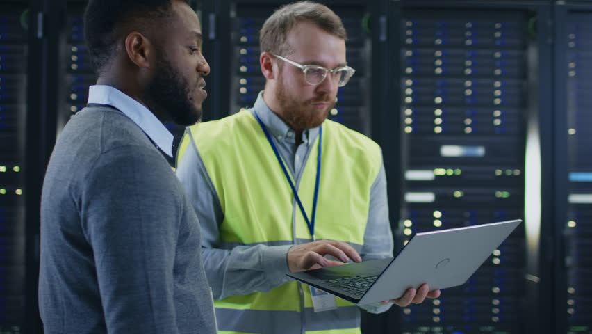 Bearded IT Specialist in Glasses and High Visibility Vest with a Laptop Computer and Black Engineer Colleague Talking in Data Center while Standing Next to Server Racks. Running Maintenance. | Shutterstock HD Video #1021974670