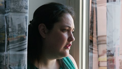 depressed overweight woman looking out the window: troubled overweight woman