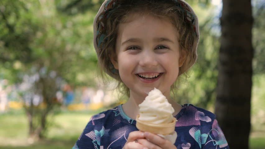 A cute little girl enjoys a delicious ice cream cone during the summer. Child with ice cream on a walk in the city park | Shutterstock HD Video #1022025940