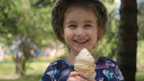 A cute little girl enjoys a delicious ice cream cone during the summer. Child with ice cream on a walk in the city park