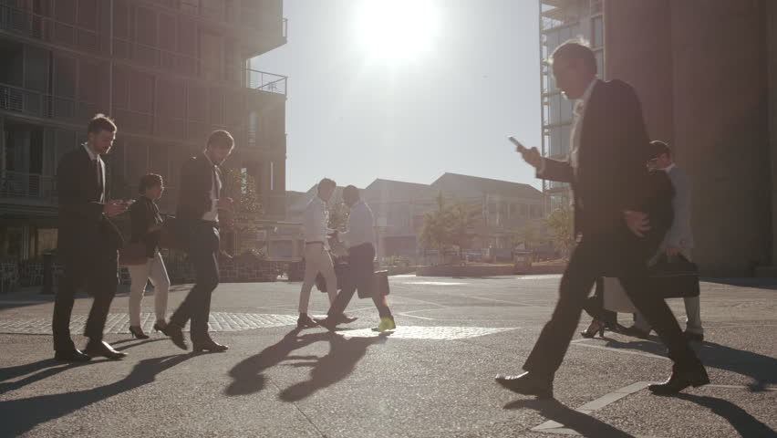 Office going pedestrians using their phones while commuting. Commuters being on their mobile phones walking to office.