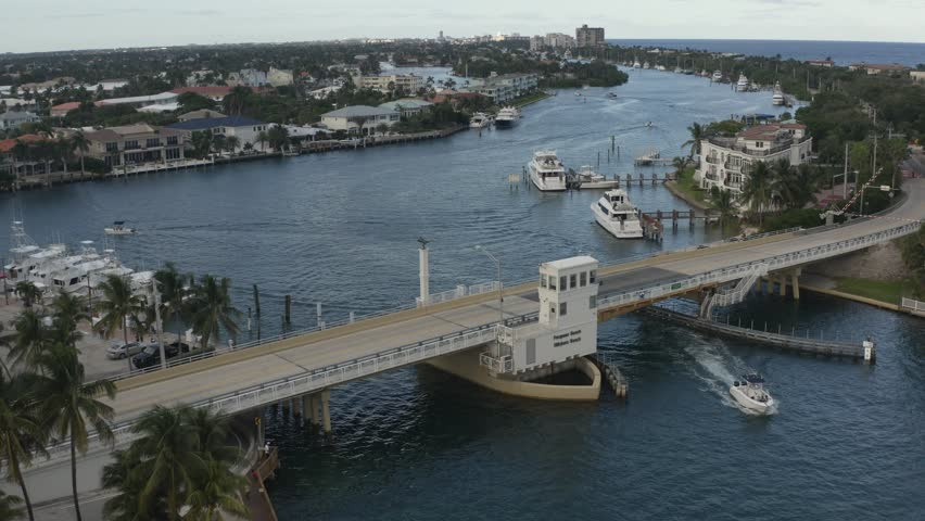 Aerial view of bridge with some carsing across then the bridge starts to rise for oncoming water traffic   Shutterstock HD Video #1022068510