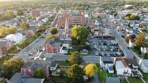 Drone descends on urban houses in small town America at Golden Hour