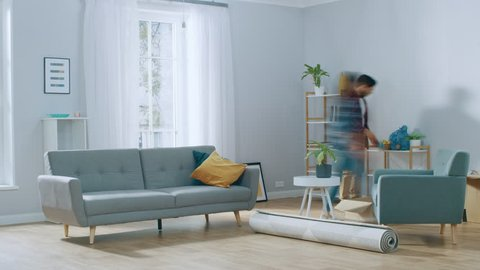 Time-Lapse: Happy Young Couple Moves into New Apartment, Arranges Furniture, Hanging Paintings, Resting after Everything is Done. Bright Modern House with Big Windows and Stylish Furniture.