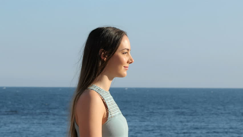 Side view portrait of a happy woman relaxing breathing fresh air on the beach