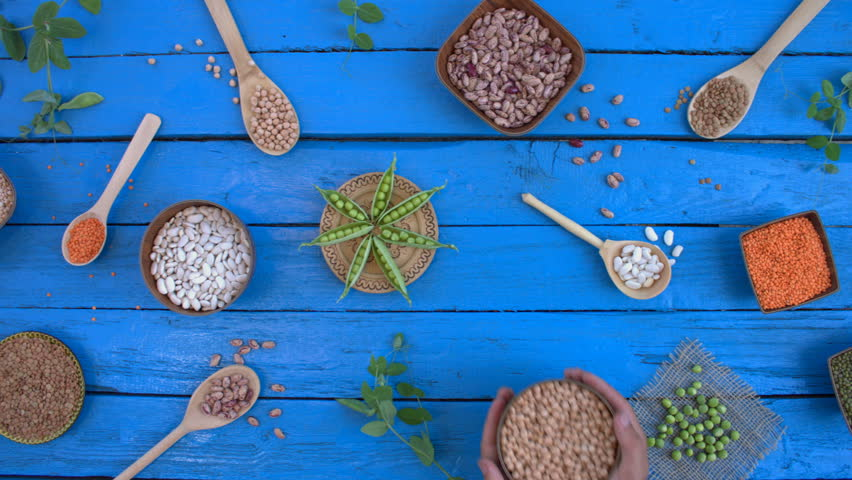 Legumes on wooden ecological background. Beans are located in unusual form on blue wooden table. Hands put bowl with chickpeas on table. Bean cultures in wooden bowls. pea lies on napkin. | Shutterstock HD Video #1022098990