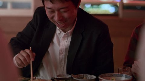 Content Japanese man eating tempura shrimp and talking with his friends on a boat with soft interior light. Close up shot on 4k RED camera.