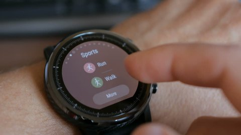Young man making gestures on a wearable smart watch computer device, smartwatch closeup. Man using her smartwatch touchscreen wearable technology device.