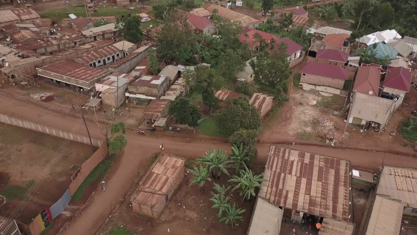 Aerial shot looking over houses in a poor community in Africa with birds flying around.