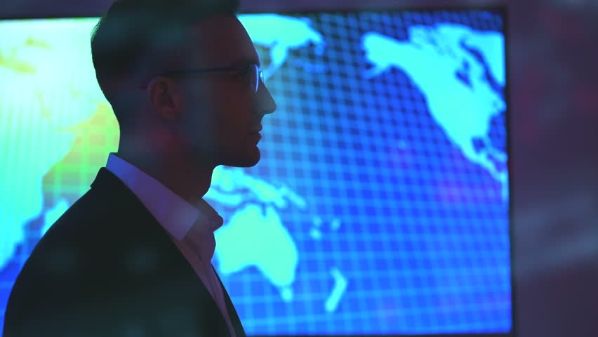 The businessman in glasses standing near a big display on a hologram background