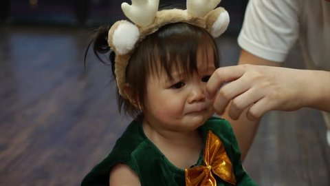 Cute Caucasian toddler baby girl crying out loud and father wiping away tears from her cheeks at home