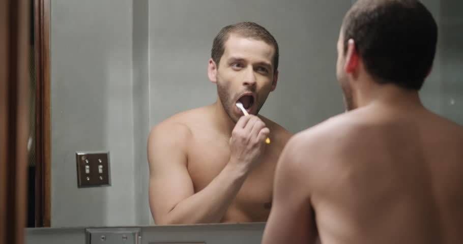 Latino gay person with beard grooming in bathroom at home for morning  routine and body care. Handsome adult metrosexual man brushing teeth and  looking at ...