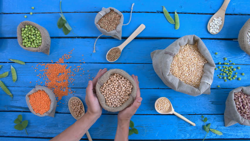 Legumes on wooden ecological background. Beans are located on a blue wooden table. Hands put woven bag with chickpeas on table.  | Shutterstock HD Video #1022202400