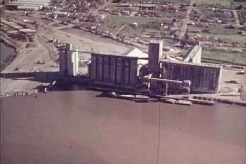 CIRCA 1973 - An aerial view of an inland port is shown as a freighter comes in.