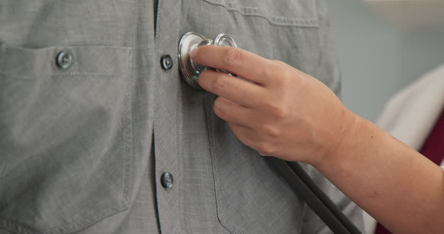 Extreme close up on hands of doctor placing stethoscope on chest of male patient to hear heart rate and breathing. Slow motion 4k