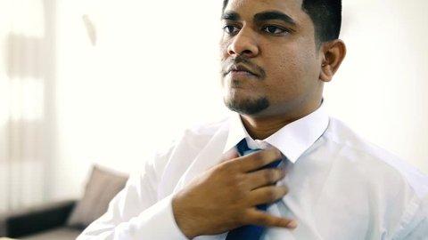 Male hindu wearing a tie, black man straightens his tie