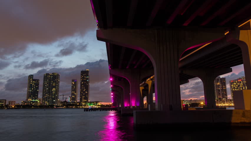 Day to night sunset timelapse hyperlapse view I-195 Highway Bridge in Miami. Concrete pillar and skyscraper buildings. Light reflection in the bay water.