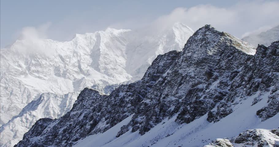 Wide shot POV AERIAL View of K2 Mountain snowcapped cold rocks and mountain peaks in Nepal near Mount Everest in Tibet