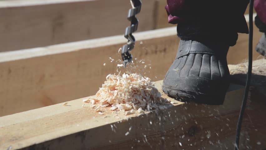 Carpenter is drilling timber wood and hammer wooden nail into timber at house construction. | Shutterstock HD Video #1022325160