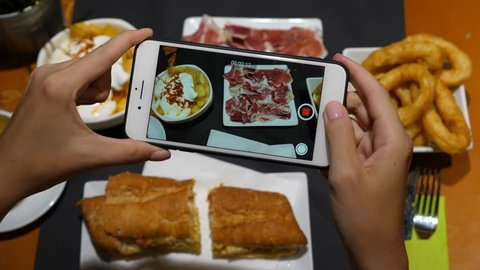 BARCELONA, SPAIN - AUGUST 17, 2018: Woman filming tapas food on lunch table using smartphone, top view. Vlogger tourist share meal served at Spanish restaurant