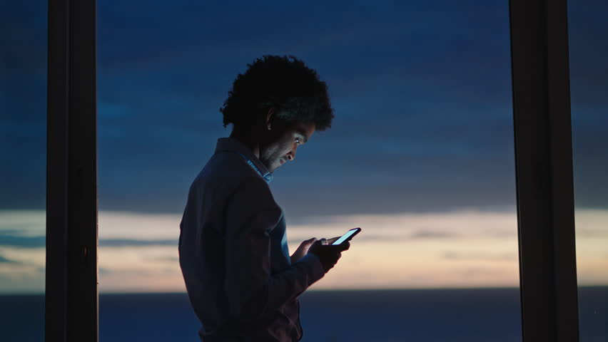 Young man using smartphone in hotel room texting sharing vacation lifestyle on social media enjoying view of ocean at sunset | Shutterstock HD Video #1022366770