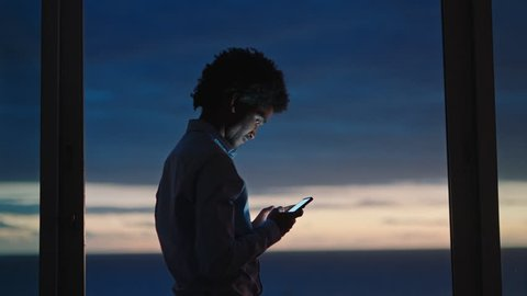 young man using smartphone in hotel room texting sharing vacation lifestyle on social media enjoying view of ocean at sunset