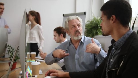 Older male mentor helping teaching new employee explaining intern giving instructions in office, senior corporate leader teacher executive training young worker listening learning new skills at work