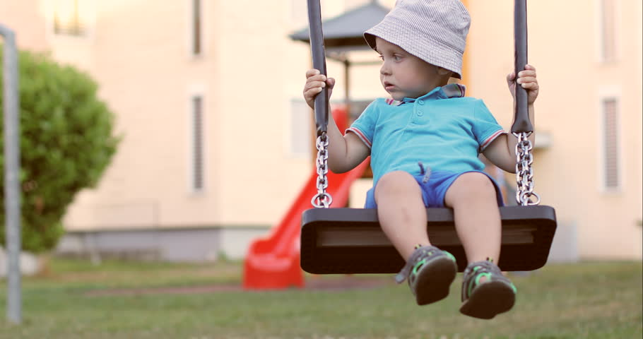 Cute little boy riding on a swing in the playground. Cheerful child resting in the park in the summer.