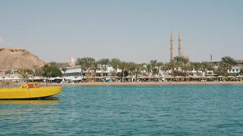 Sharm el Sheikh, Egypt - October24, 2018: Impressive view of a long yellow ship floating along the picturesque seacoast with a lot of hotels and palms in Sharm El Sheikh on a sunny day in slow motion