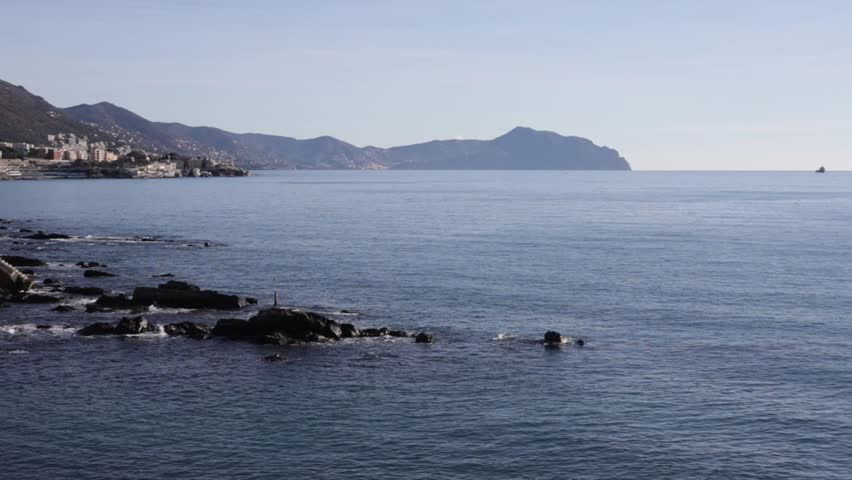 View on the Promontory of Portofino from boccadasse, with the sea breaking on the rocks and perspective of the coast