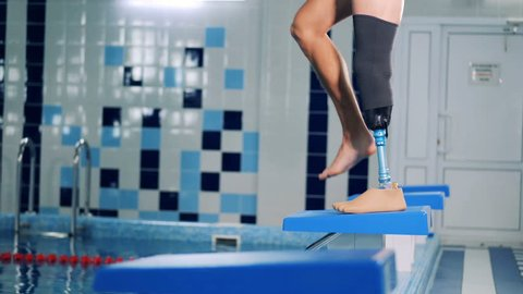Male swimmer with prosthetic leg warming up, side view.