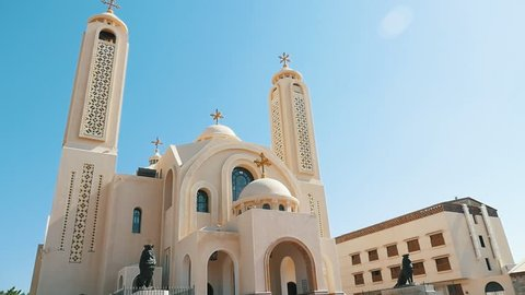 Sharm el Sheikh, Egypt - October24, 2018: Stunning view of Coptic Christian Church of Sharm-el-Sheikh with spherical domes, a dark monument and two high towers in Egypt on a sunny day in slow motion