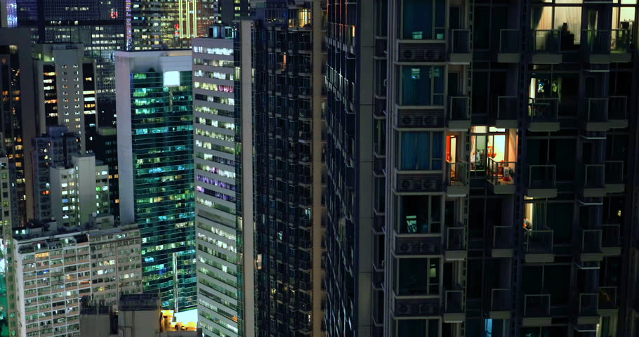 Modern city downtown at night. Apartments, condos and office buildings illumination in Hong Kong aerial view