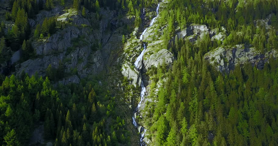 Aerial locked in shot of a mountain waterfall in the Italian alps with water falling of a cliff of a mountain. | Shutterstock HD Video #1022524480