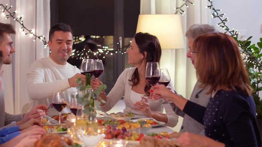 Celebration, holidays and people concept - happy family having dinner party, drinking red wine and toasting at home | Shutterstock HD Video #1022556460