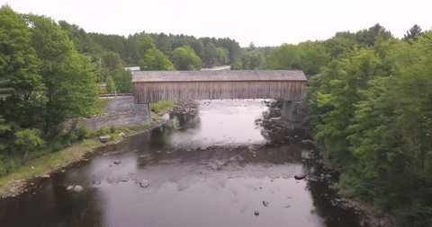 Aerial shot flying above the Piscataquls River and a wooden covered bridge in Maine.