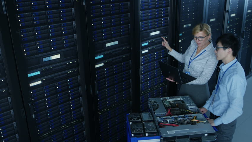 In the Modern Data Center: Engineer and IT Specialist Work with Server Racks, on a Pushcart Equipment for Installing New Hardware. Specialists Doing Maintenance and Diagnostics of the Database.  | Shutterstock HD Video #1022590750