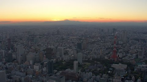 Tokyo, Japan circa-2018. Flying over Tokyo Tower as sun sets behind Mount Fuji. Shot from helicopter with RED camera.