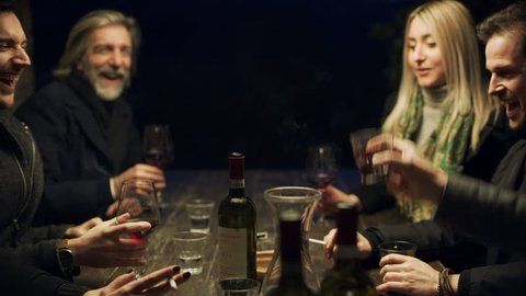 Group of Italian friends sitting outside at a table drinking wine and smoking cigarettes and talking and laughing together with soft night light. Medium shot on 4k RED camera.