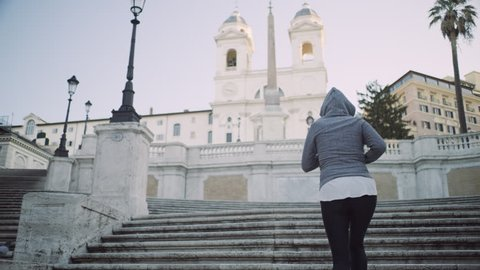 Active Italian woman running up the Spanish Steps passing a group of tourists to the top. Wide shot on 4k RED camera.