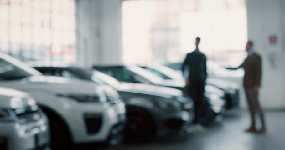 Dealer and new owner handshake after concluding a car deal in auto show or salon. Slow motion shot in 8K. Concept of car dealerships, used cars, car sale and rent, auto deal.