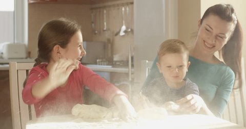 Smiling Happy Family Playing with Dough Banging on the Flour on the Table in the Kitchen Cooking Together Cookies. Cheerful Mother Son and Daughter Having Fun and Good Time on a Sunny Day