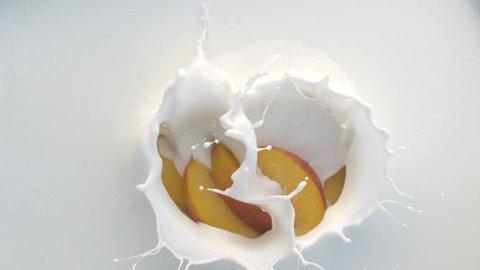 Peach Falling Down into Yogurt or Milk Creating Splashes in Slow Motion. Top View Shot on High Speed Phantom Camera