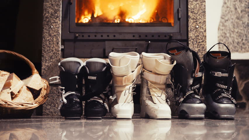 4K Static footage of three pairs of skiing boots standing next to the fireplace. Winter holidays concept.