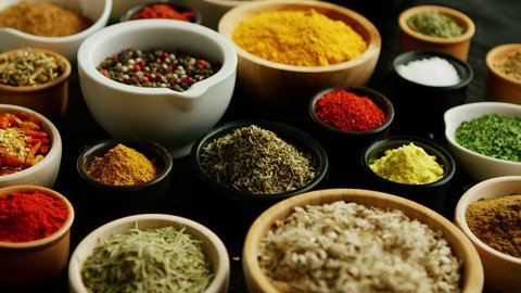 From above view of many little bowls with different kinds of spices laid on wooden background